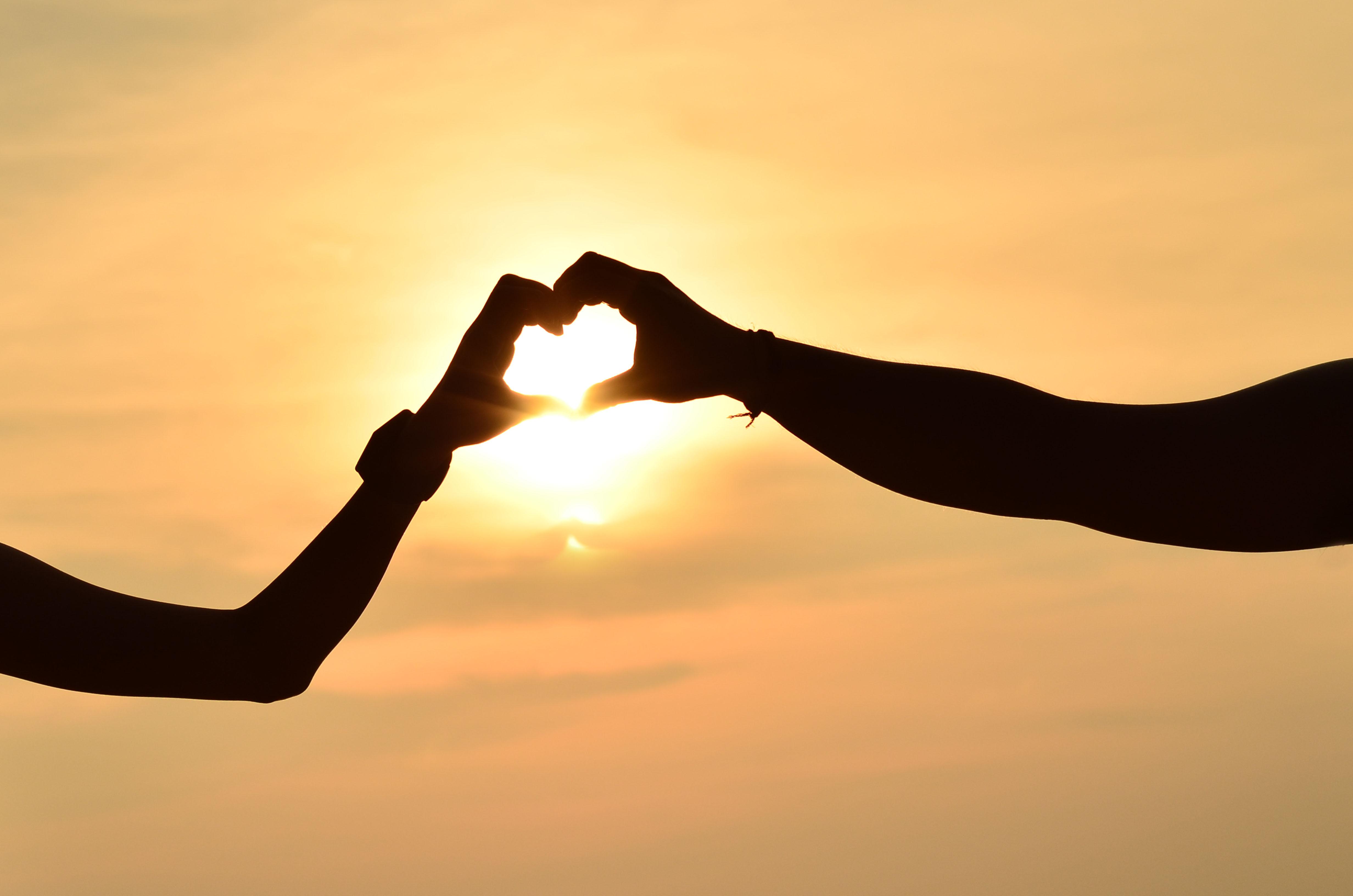 Două mâini care țin soarele